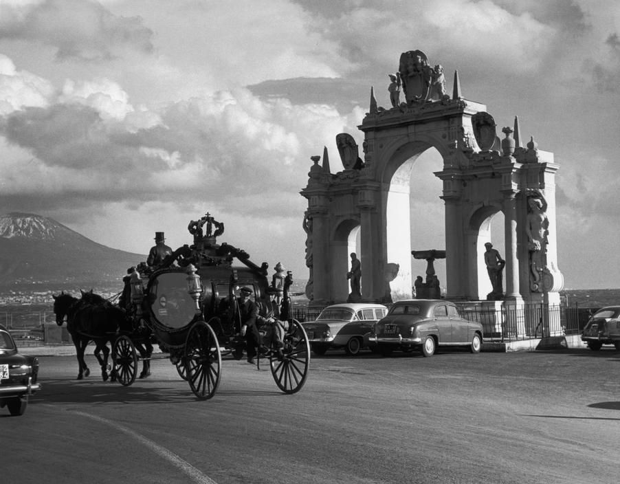 Herbert List View profile ITALY. Naples. 1958. Hearse on the promenade in front of the Fountain of Santa Lucia.