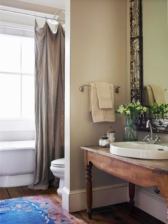 Simple and elegant bath - I love wood floors throughout a house. Using an old table as a new one-of-a-kind sink counter is giving it new life. Plus, great area rug too!