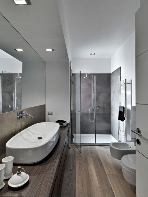 Long Narrow Bathroom With Wood Floor, Wood Counter, Glass Shower And Large  White Sink