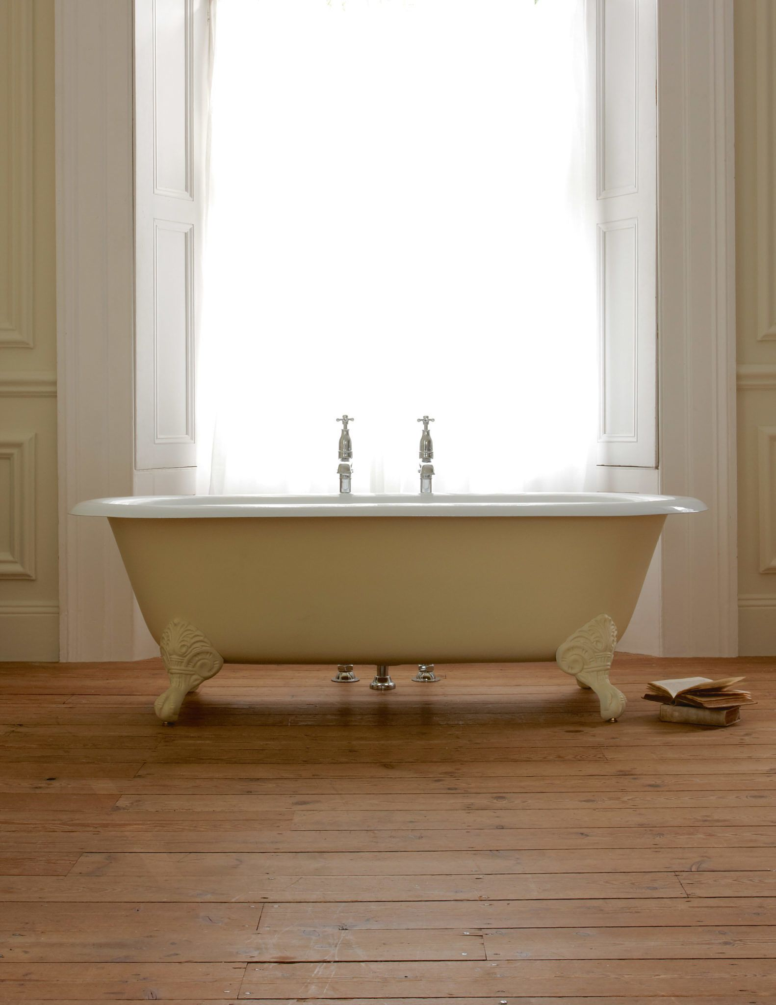 A large double ended cast iron bath tub featuring a wide roll top ...