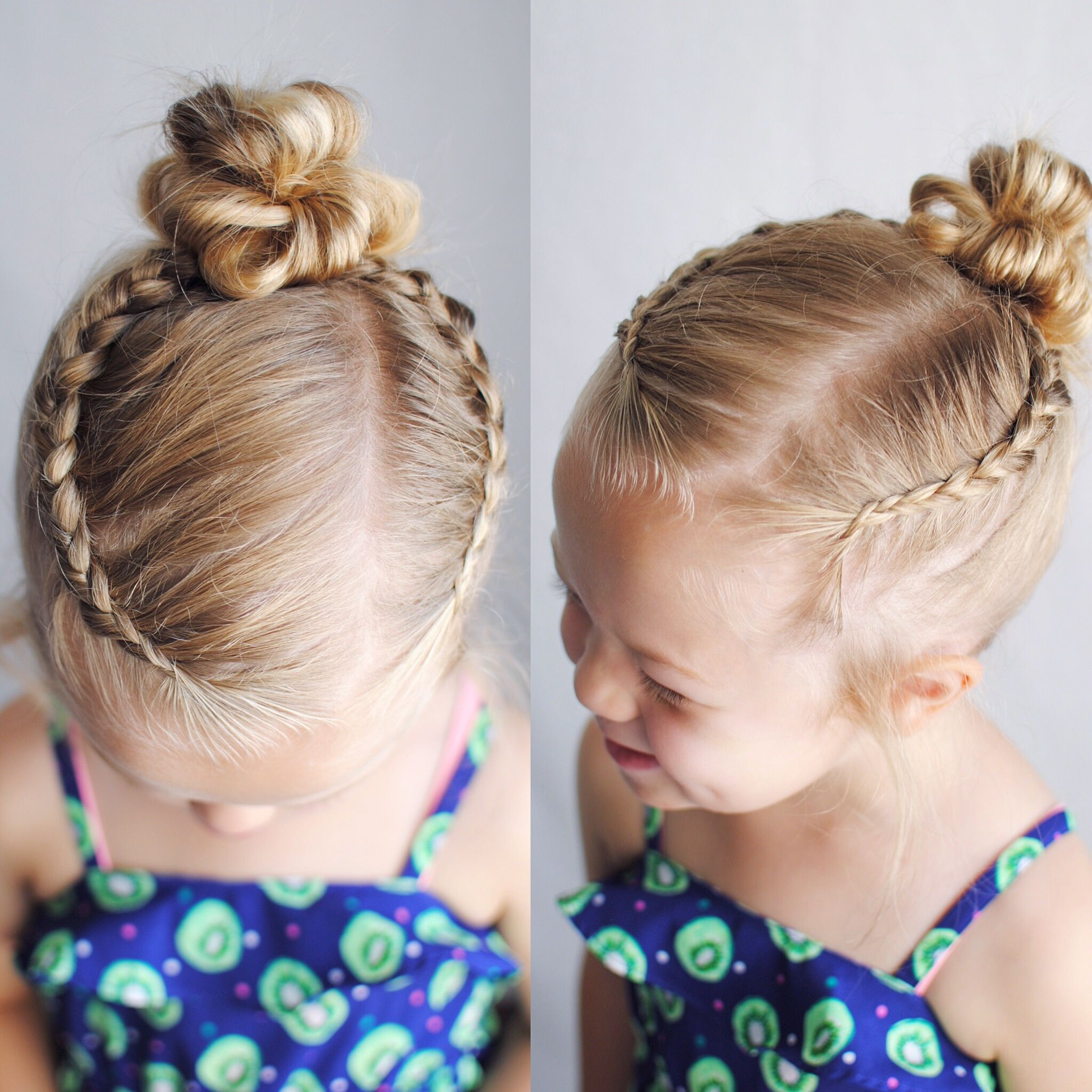 Two Dutch braids parted into a top knot or messy bun