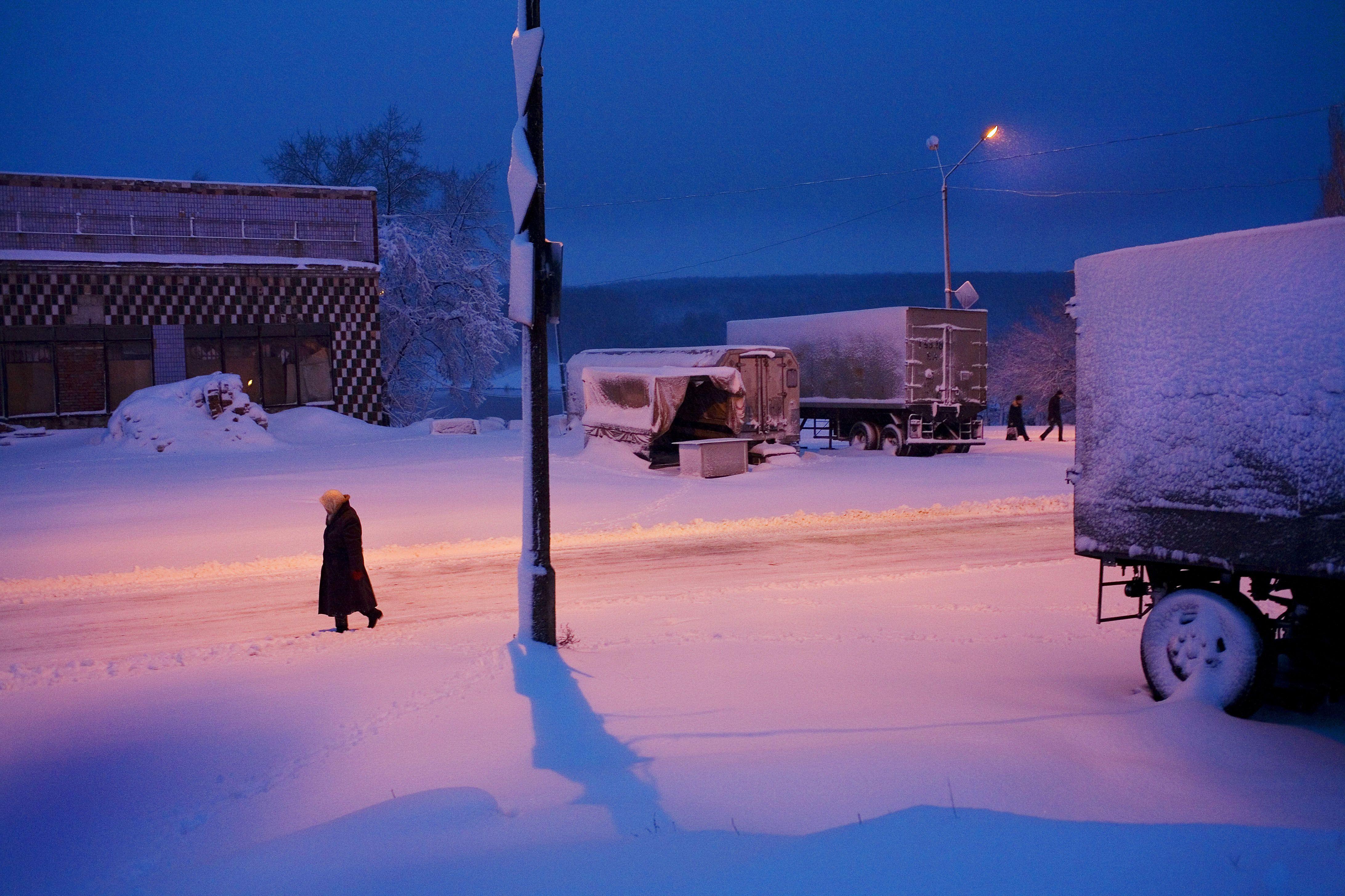 UKRAINE. Torez, Donetsk Oblast. 2007. A woman walks in the snow at dawn in winter. (© Carolyn Drake/Magnum Photos)