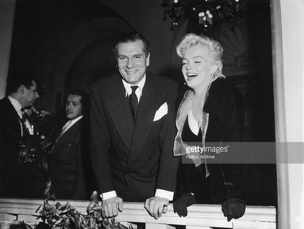 1957: British actor Sir Laurence Olivier (1907 - 1989) and American actor Marilyn Monroe (1926 - 1962) stand and lean over a railing on a balcony, laughing. She wears a black coat and gloves.