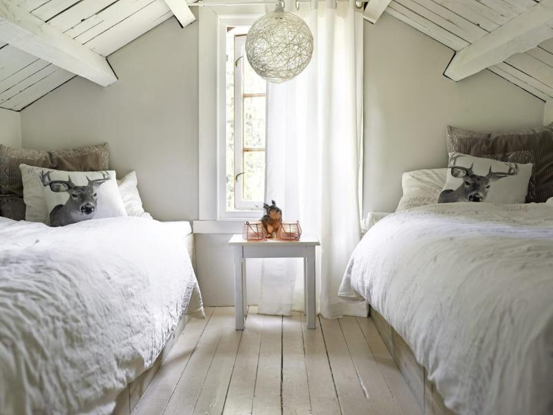 SELVSNEKRET: Hytteeieren har selv sneret de to sengene på jenterommet. Rommet er malt i lyse farger, og har lyse tekstiler.