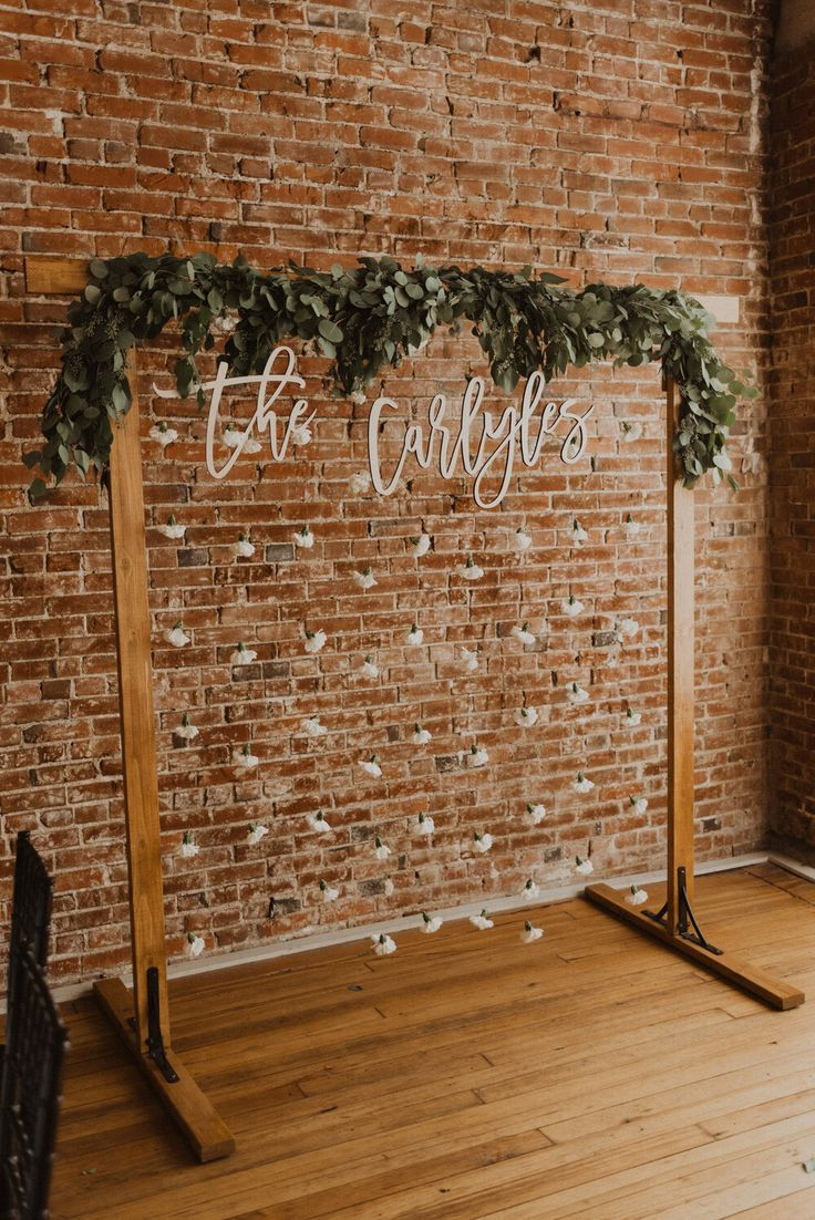 cute boho diy photo booth ideas with wooden frame and seeded eucalyptus greenery. hand lettered last name sign. white carnations string kansas city wedding photography  www.alyssabarletter.com
