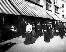Late 19th-century commercial streetscape with women walking next to striped awnings. & Late 19th-century commercial streetscape with women walking next ...