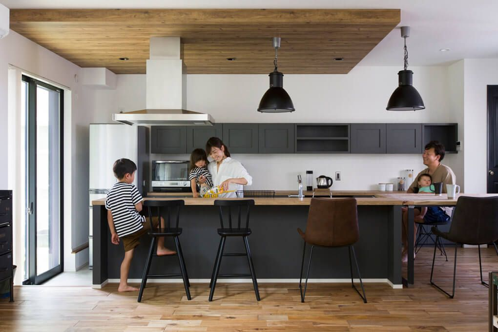 古材で造ったダイニングテーブルに合わせてキッチン カウンターの色やデザインを決めたため まるでつながっているかのような一体感 構造上下げる必要があった天井は 木目調にして空間のアクセントに リビング キッチン キッチンカウンター インテリア 黒 キッチン
