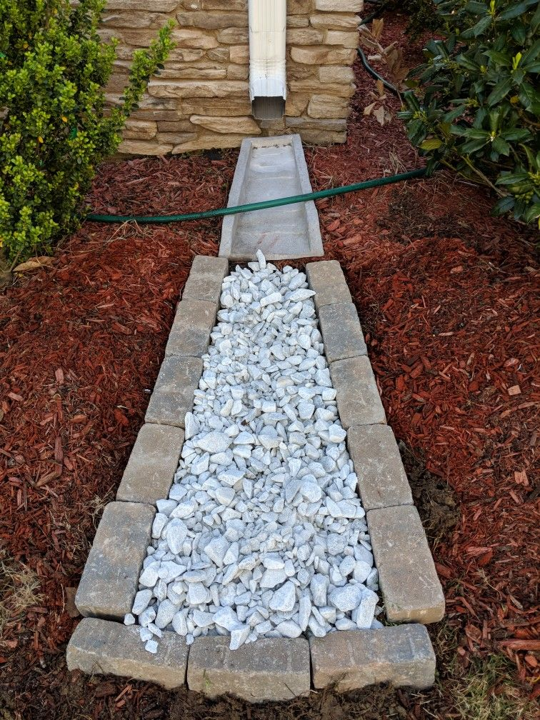 Downspout Drainage With Marble Rocks Keeps The Mulch From Sliding Out Of Place 0 92 Ea For The 3 5x7 Bord Marble Rock Landscape Projects Downspout Drainage