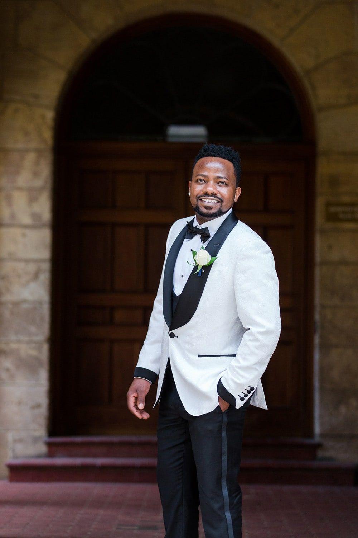 Modern black groom wearing stylish white tuxedo with black
