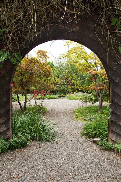 Bohemian Country Rustic Garden: A shingled archway leads to a rustic garden .