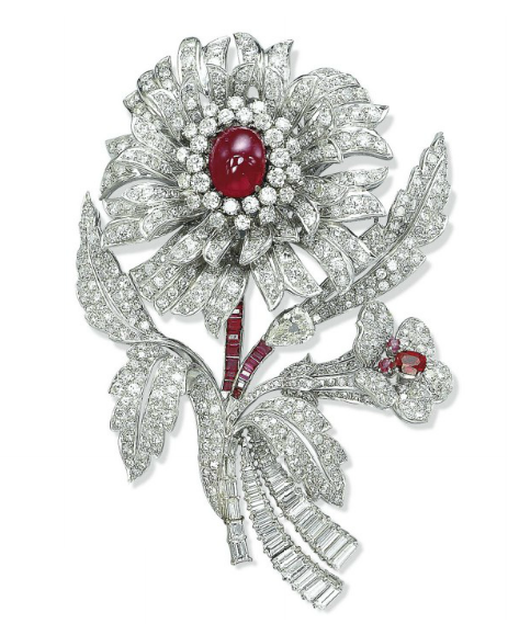 A RUBY AND DIAMOND BROOCH   Designed as a stylized flower with pavé-set diamond petals and leaves centering upon a cabochon ruby pistil mounted en tremblant, to the calibré-cut ruby and baguette-cut diamond stem, the smaller flower also with a ruby pistil, mounted in platinum.