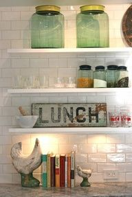 From the vintage glass canisters to the worn vintage lunch sign, theres so much to love about this space if youre a fan of general-store style. Set against the shiny white subway tiles, these vintage finds stand out as special. Thought of you @Krystal Ten Kley