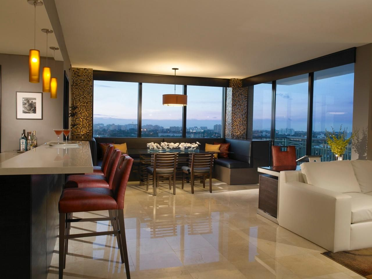 This modern dining room with an open floor plan is perfect for entertaining with an oversized banquette that seats 10 and bar area. Floor to ceiling windows offer a stunning panoramic view of the city skyline creating a perfect backdrop.