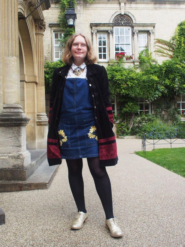Hannah wears a denim jumper dress with embroidered pockets