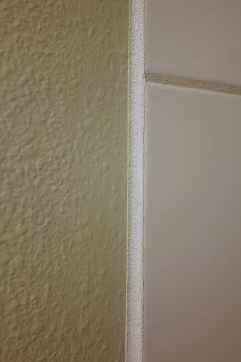 tape 1/8 inch away from edge of tile... caulk edge... run finger ...
