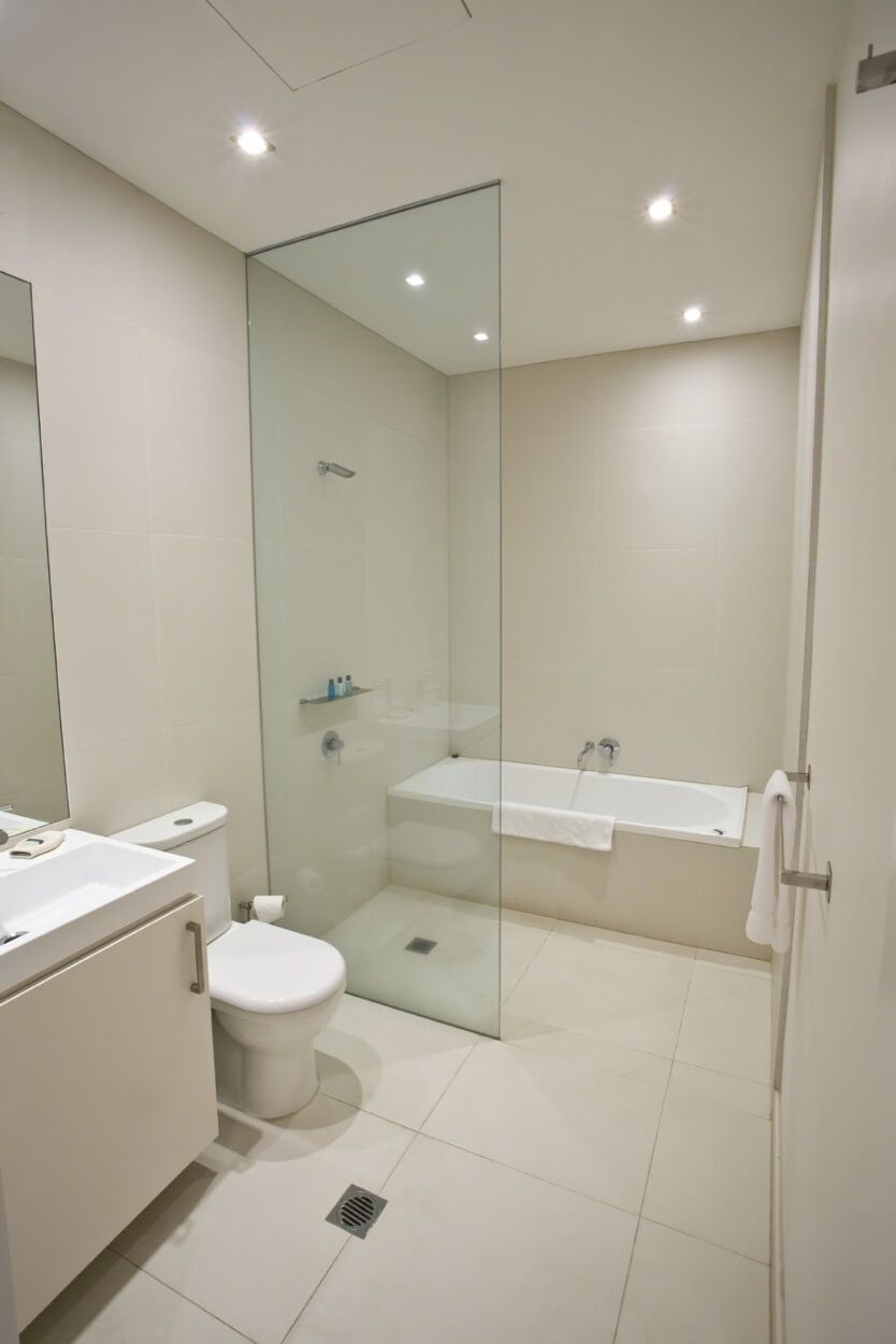 cream colored bathroom with glass dividing wall  wet room