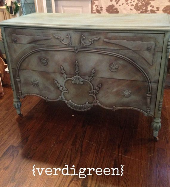 This Depression Era dresser is a beautiful example of early 21st century wood working. We love the ornate embellishments and femme details and seeked to preserve them with our hand-painting and waxing.  This is a lovely color called Provence by Annie Sloan - a high end non-toxic decorative paint - and its washed with color and an antiquing wax to give it painterly character. Original wooden casters.  50.5″L x 22″ W x 35″ H  Come see it in person at our Montclair location (182 Glenridge Ave…
