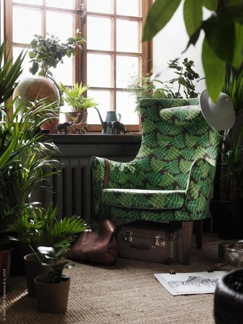 A plethora of plants and a floral-printed IKEA armchair create a peaceful oasis in an urban jungle. | thisoldhouse.com