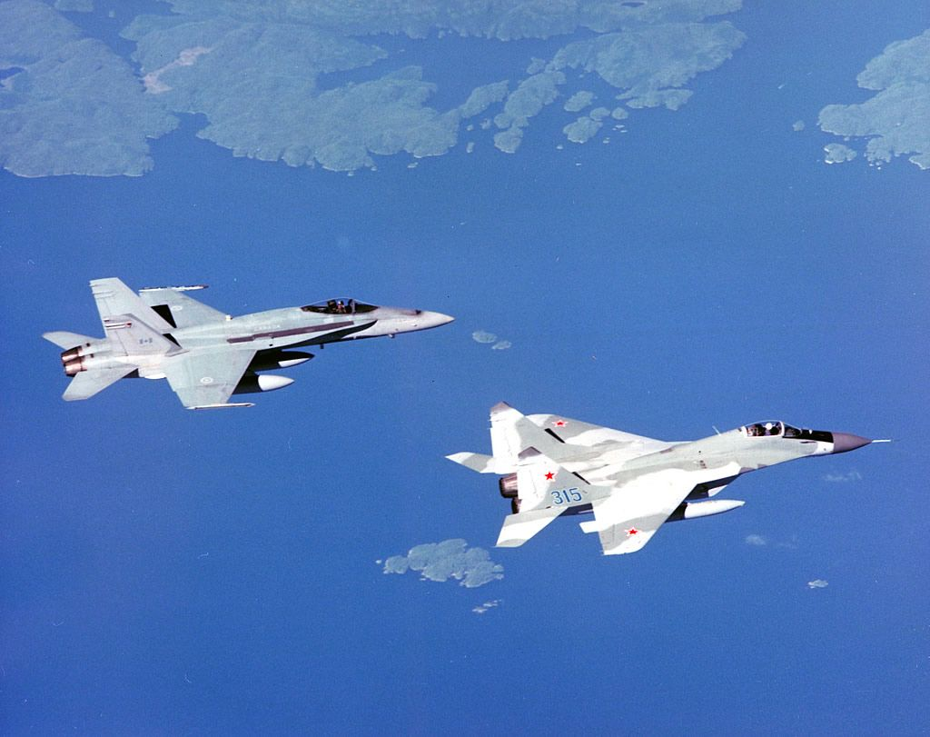 """Royal Canadian Air Force CF-18 Hornet in formation with Russian Air Force Mikoyan Mig-29 """"Fulcrum""""."""
