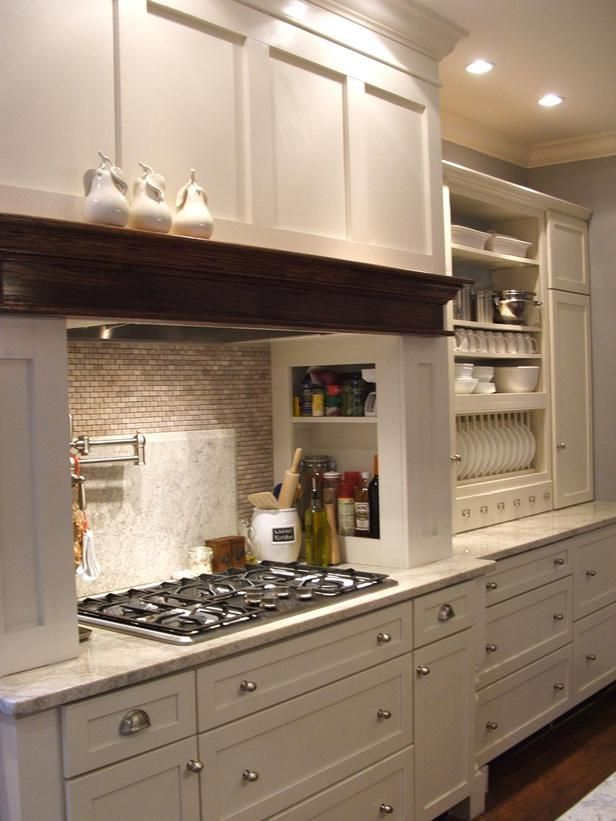 To save money, this HGTV fan built a range hood out of plywood and then painted it to match her existing cabinets. She also purchased unfinished table legs online, painted them and added them to the base of her cabinets.