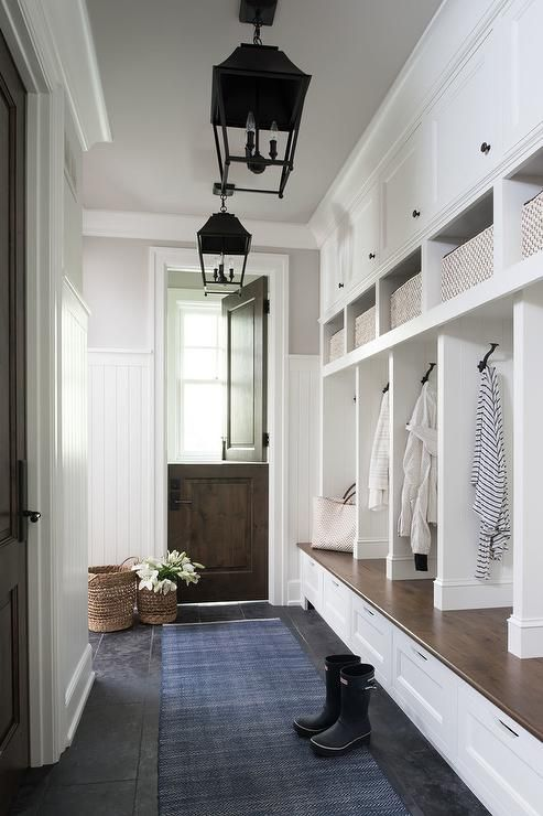 A Walnut Dutch Door Flanked By A Vertical Beadboard Trim Opens To A Blue Runner Lit By Two
