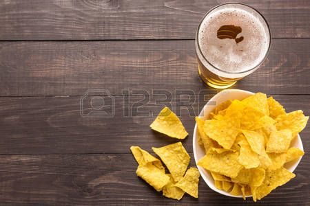 beer: Glass of beer with nachos chips on a wooden background.