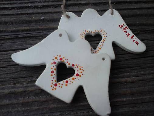 Anjelik je vlastnoručne vyrobený z bielej keramickej hmoty. V strede má otvor v tvare srdca, ktorý je ozdobený červeno-oranžovými bodkami namaľovanými akrylovou farbou. Z oboch strán je via...