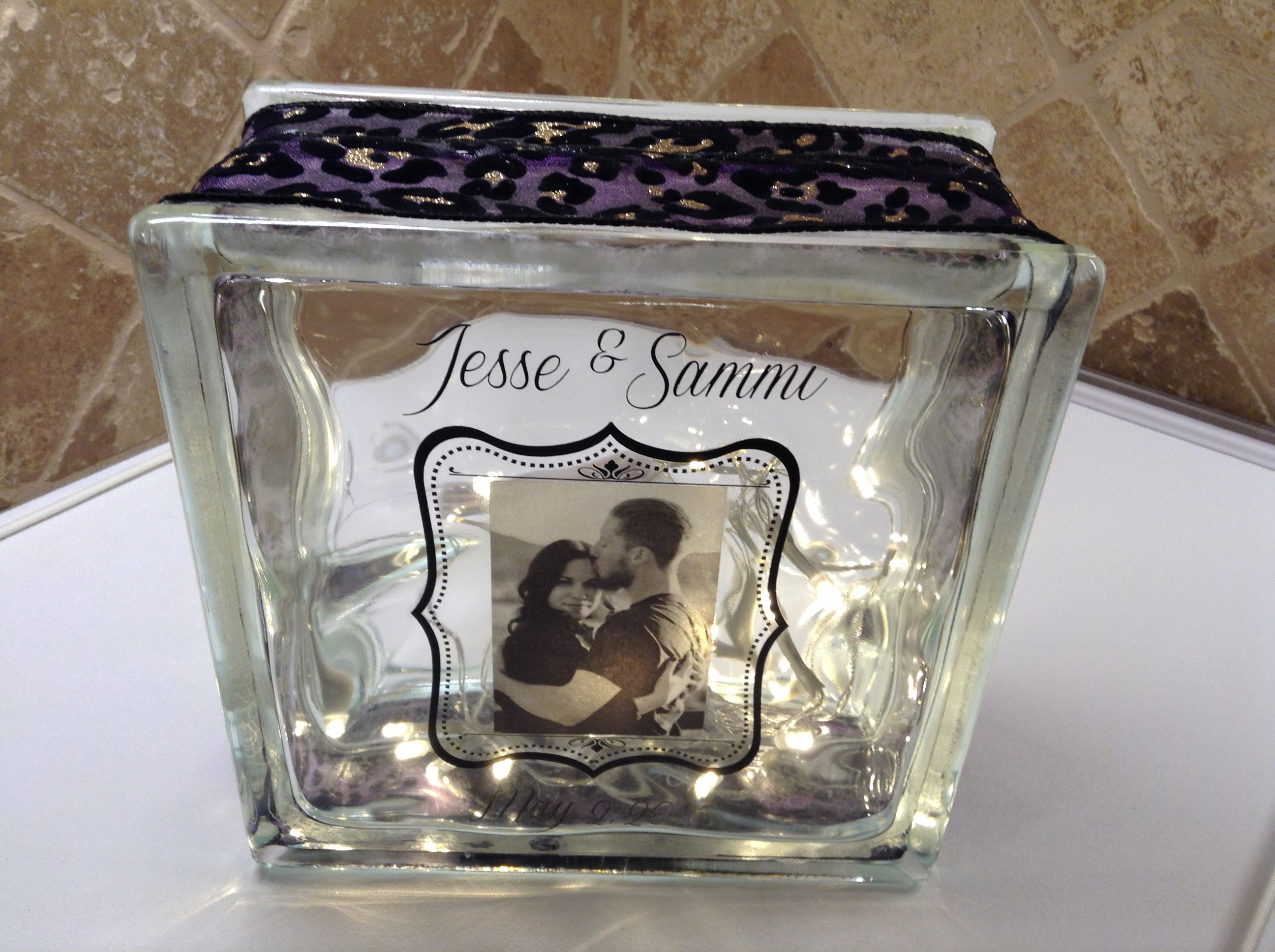 SPECIAL ORDER GLASS LIGHT BLOCK WITH LASER ETCHED BRIDGE/GROOM DETAILS, PURPLE/BLACK CHEETAH RIBBON EMBELLISHMENT, PERSONAL PHOTO AND WARM LED BATTERY OPERATED LIGHTS.