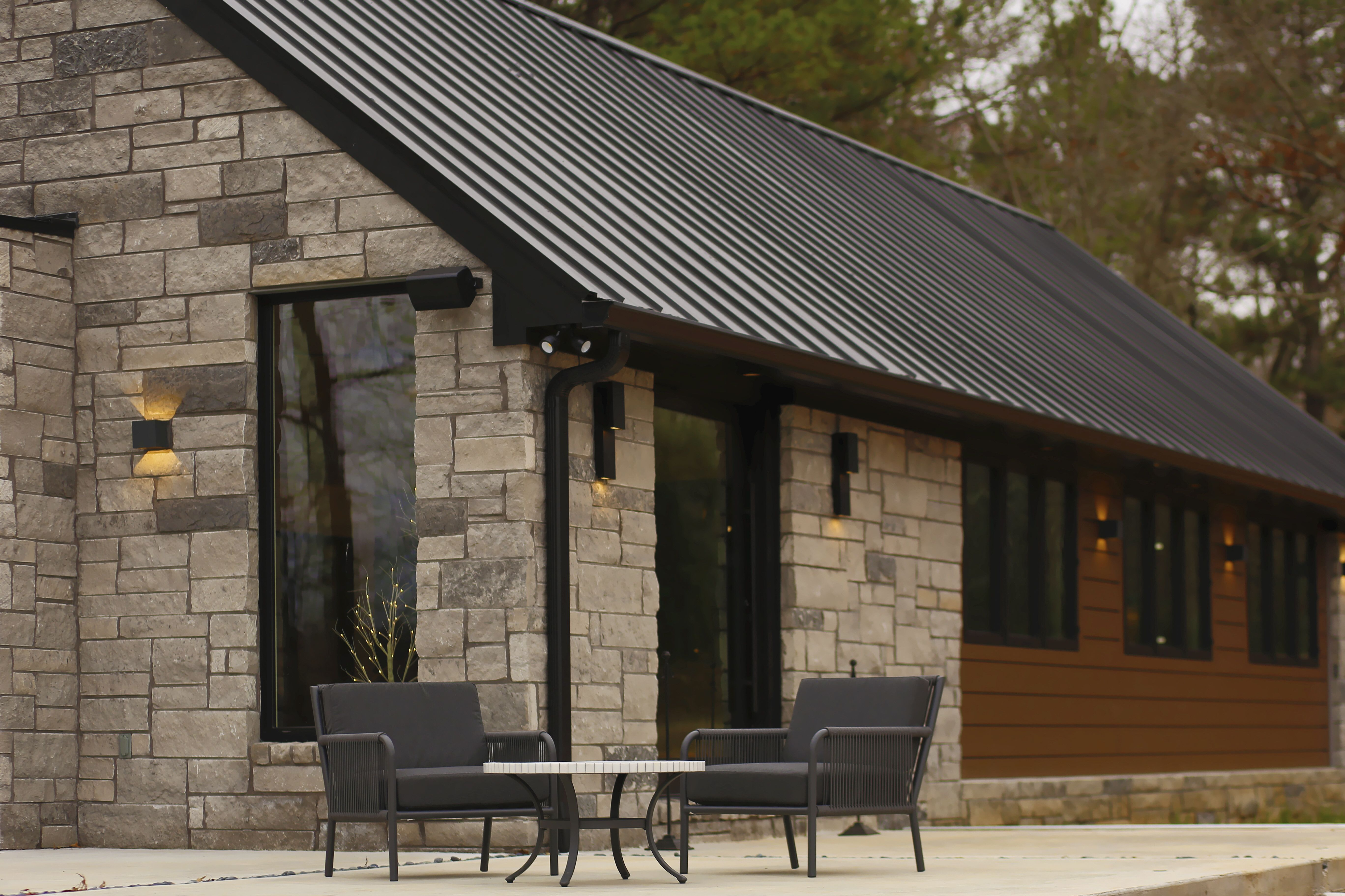 View From Concrete Patio With Gray Rock And Black Roof House Designs Exterior House On The Rock Black Metal Roof