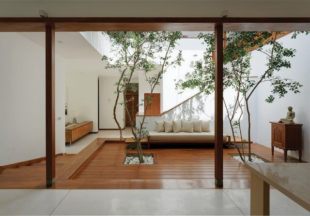 Open plan living space centered around a brightly lit indoor courtyard with trees in a breezy residence Sri Jayawardenepura Kotte Sri Lanka By Lalith Gunadasa Architects