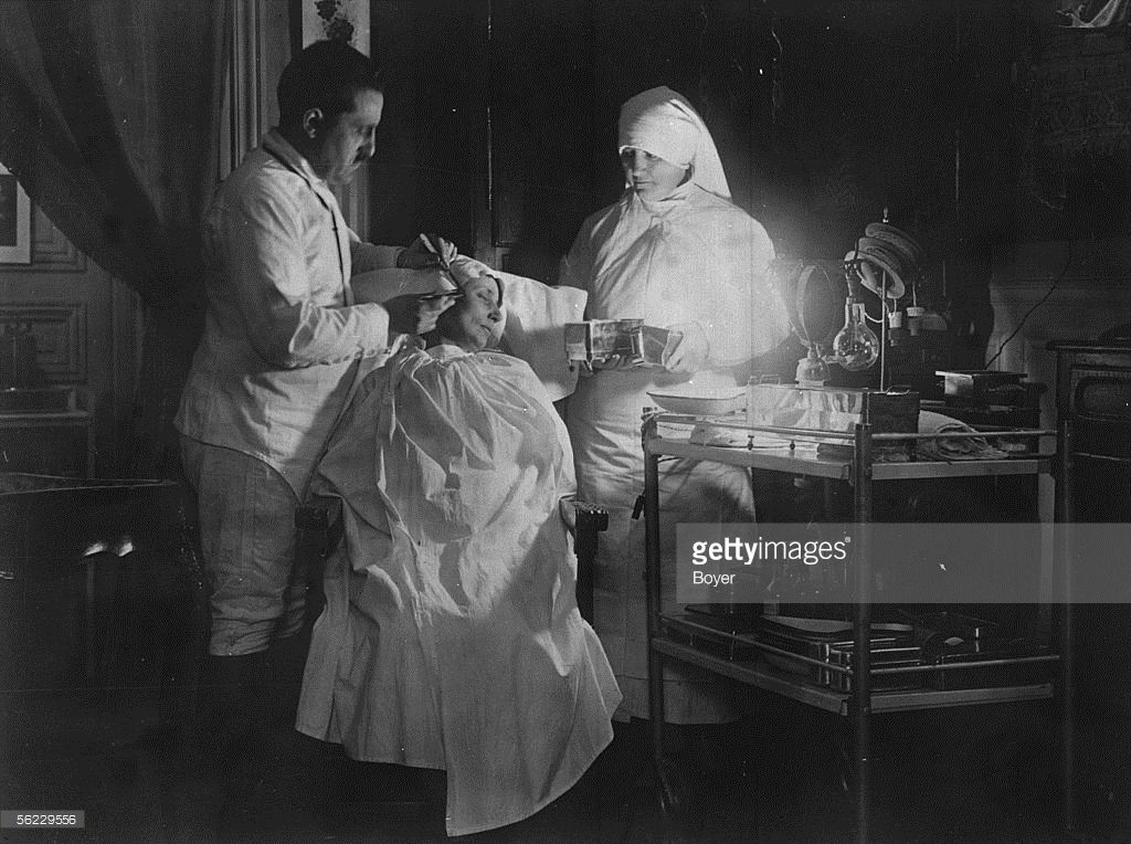 Plastic surgery. The doctor Bouchon. Incision of the skin folds to remove (the doctor must operate with the ultra-violet light). Paris, 1927. BOY