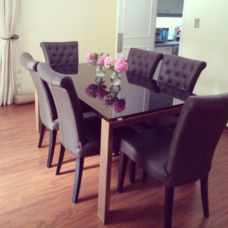 Mesa de comedor de vidrio con sillas de cuero marrón ...