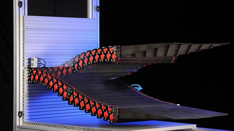 Wissenschaftler des Deutschen Zentrums für Luft- und Raumfahrt (DLR) forschen an einer verformbaren Flügelhinterkante, die sich stufenlos in beliebige Zielformen bewegen kann und klassische Landeklappen überflüssig macht. Die Klappen an den Tragflächen heutiger Verkehrsflugzeuge werden durch eine aufwendige Mechanik betätigt. Deren Verkleidung sowie entstehende Spalte beim Ausfahren beeinträchtigen die Aerodynamik, erhöhen dadurch den Kraftstoffverbrauch und tragen zudem zum Fluglärm bei…