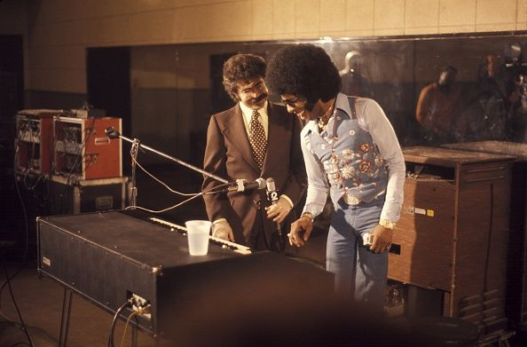 American film critic Joel Siegel and singer and musician Sly Stone of the funk band 'Sly and the Family Stone' backstage at Radio City Music Hall on...