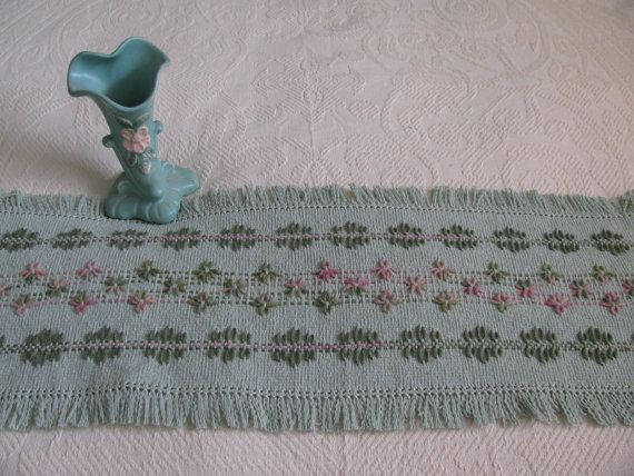 Highlight your table or dresser with this sage green runner. It is made of 100% cotton monks cloth and decorated in a Swedish Weaving floral