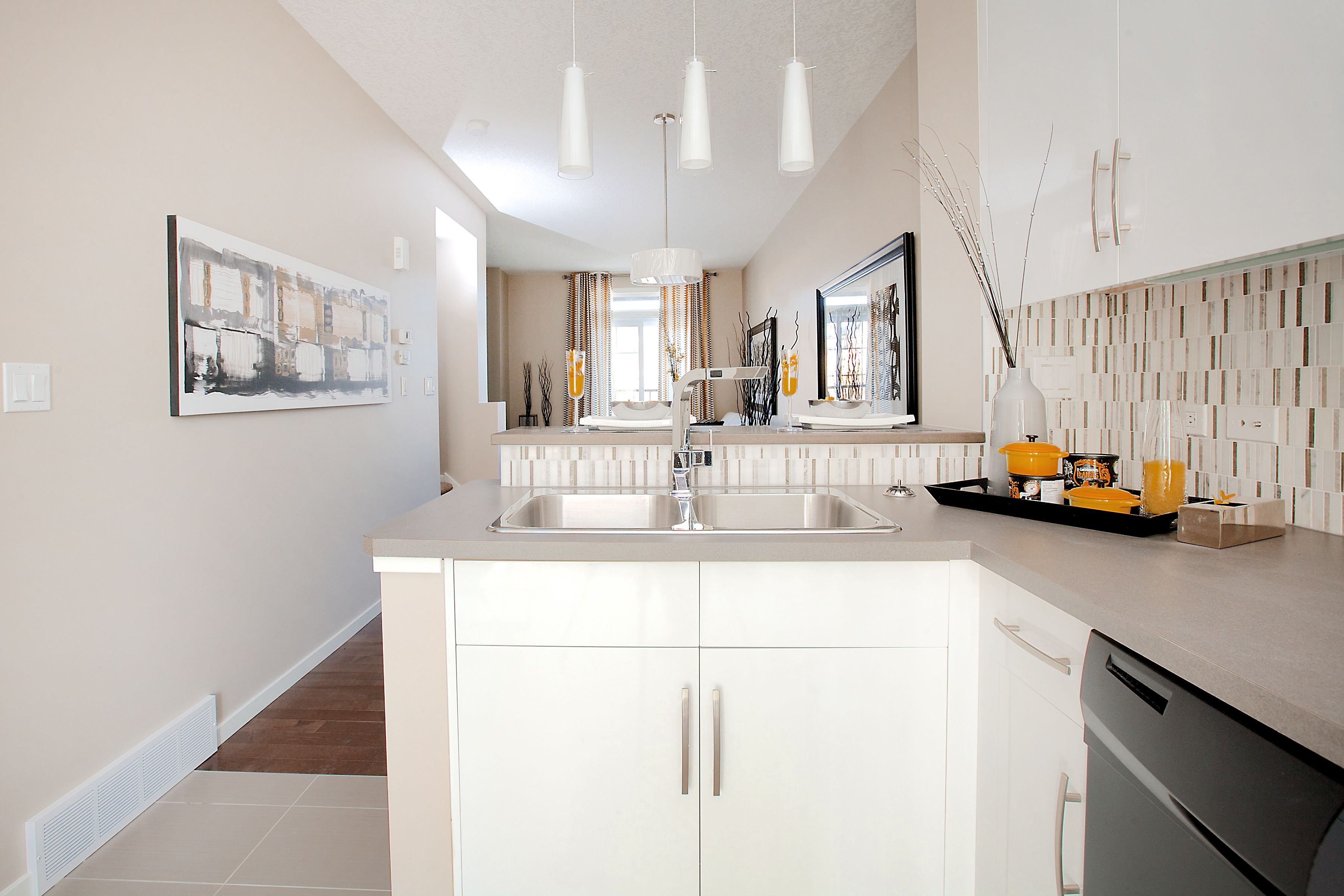 open concept l shaped kitchen with white flat panel cabinetry glass pendant lights