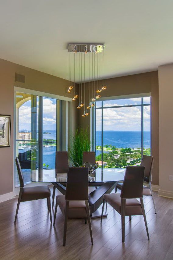 This contemporary home is furnished to accommodate its gorgeous ocean view. For this dining area, the furnishings are elegant yet understated to bring forth the beauty of the outdoors seen from the floor-to-ceiling windows that surround the space. A modern light fixture is a perfect accent to the decor.