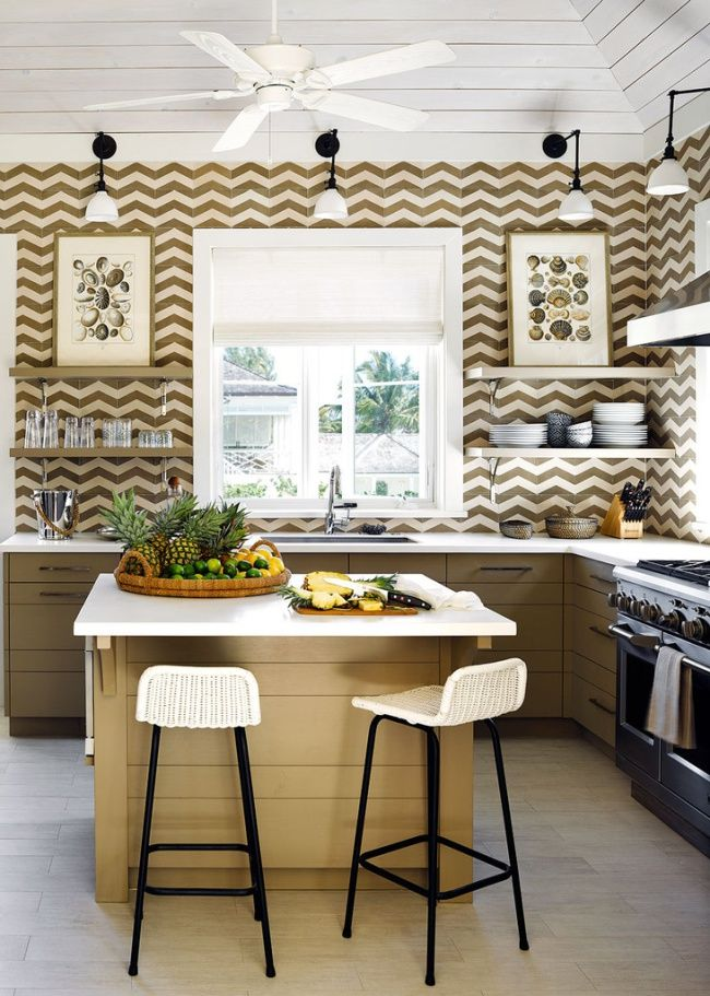 Chevron backsplash tiles all the way to the ceiling make this small kitchen lively and fun. The custom island provides additional prep space and seating.
