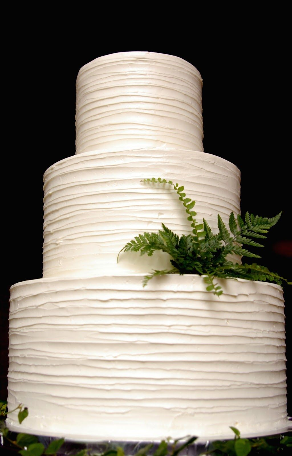 simple three tier white butter cream wedding cake