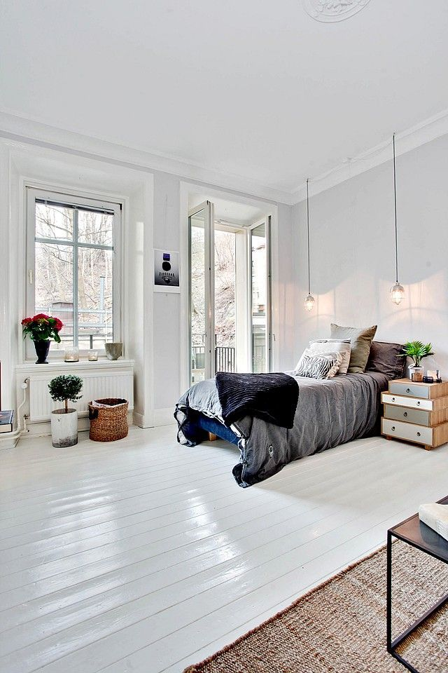 City bedroom filled with natural light. Tall French doors open out to Juliette balcony