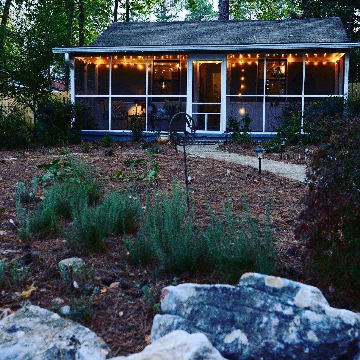 Twinkle lights come on at dusk, adding to the cottage