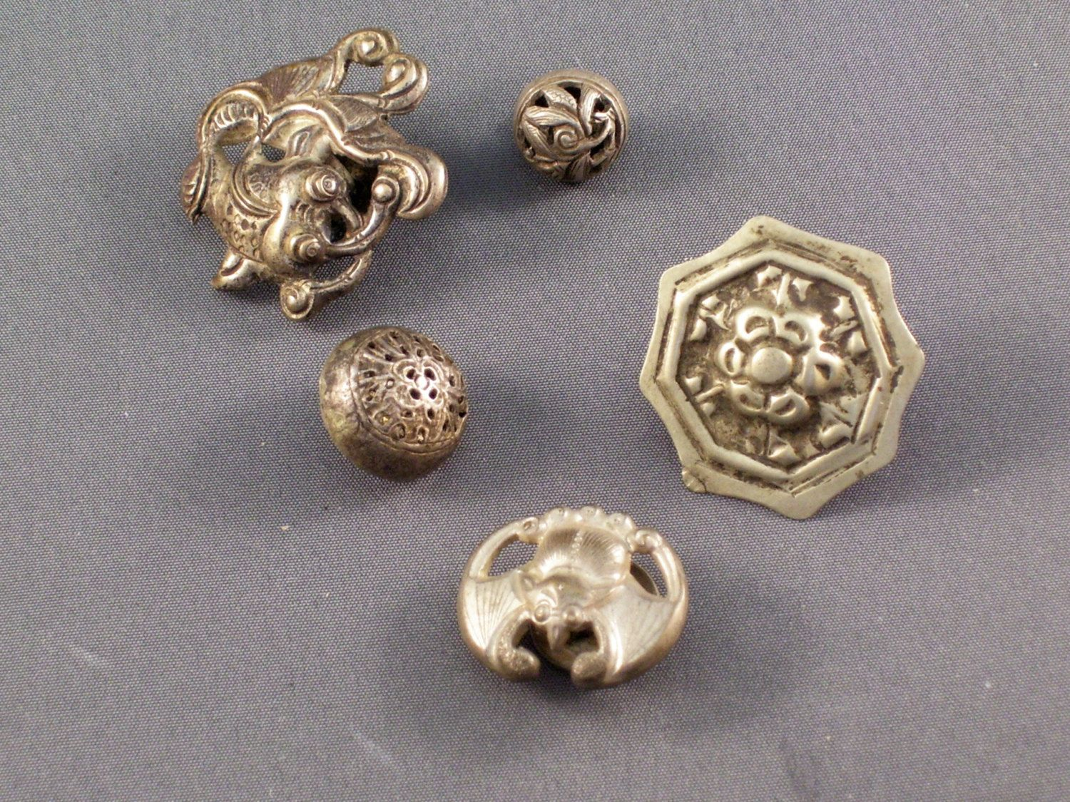 There are five assorted buttons in this group, all different motifs but featuring the same type of attachment on the back.  The largest button is