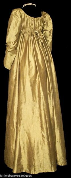 """Back view. marvelous original circa 1810 to 1815 lady's golden olive green silk satin one piece gown that was fashionable for evening wear as it was meant to be illuminated in the candle light. A fashionable high waist, an unlined bodice, a drawstring decolletage, shoulder plackets, long slender unlined sleeves with gathered shoulder tops, linen lined armscyes, underarm gussets, a one piece front and a gored skirt back, and a 1"""" turned hem to the unlined skirt."""