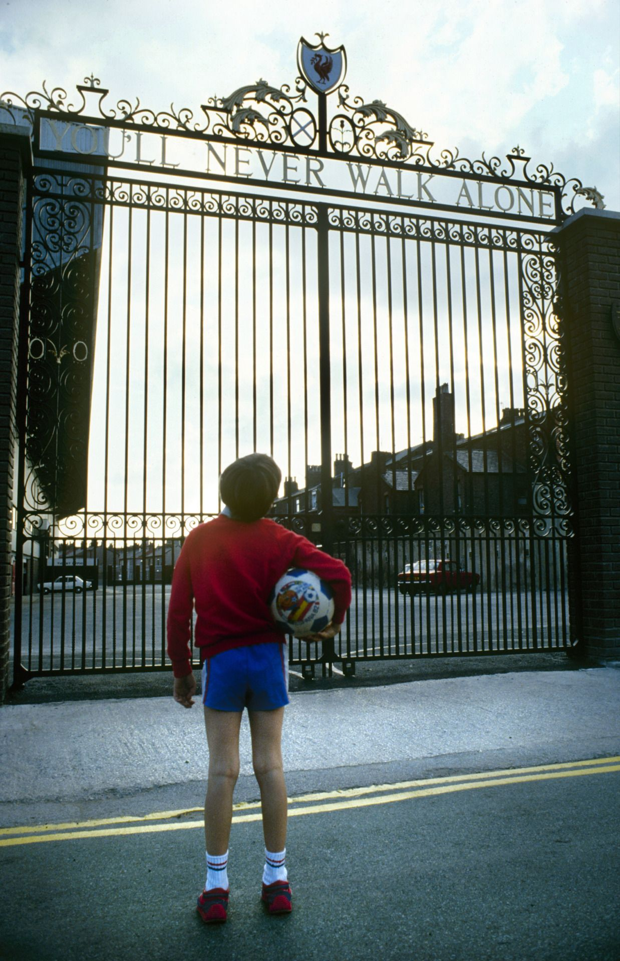 A young footballer looks up at the Shankly Gates at Anfield and dreams of pulling on the red shirt for his club during the 1980s. Photo: Steve Hale.Click here to buy this print from the Official Liverpool FC Picture Store