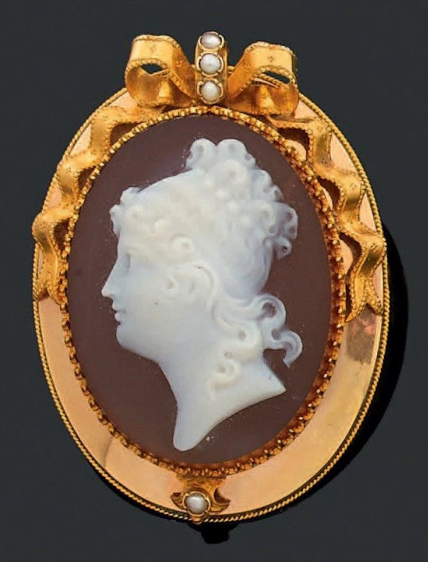 02694013e A 19th century carnelian cameo brooch, depicting a female profile, set in a  yellow gold frame decorated with a bow accent set with three half pearls.