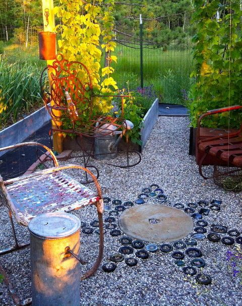 How to bury bottles to create stunning yard art is part of Outdoor garden Decoracion - Most people recycle their leftover bottles, but not this homeowner! My bottle 'sun' or 'star', depending on what time of day it is   zone 4 garden, no breakage problems, buried in sand  Recycled wine, beer, and liquor bottles)