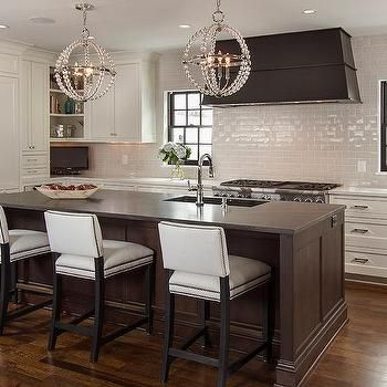 Brown Kitchen Island With Gray Sandstone Countertops And White Upholstered Nailhead Counter Stools