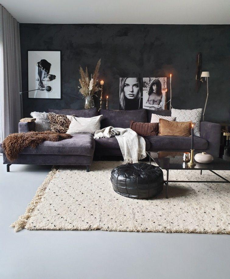 Photo of een zwarte hoekbank, zwarte muur en veel grijstinten
