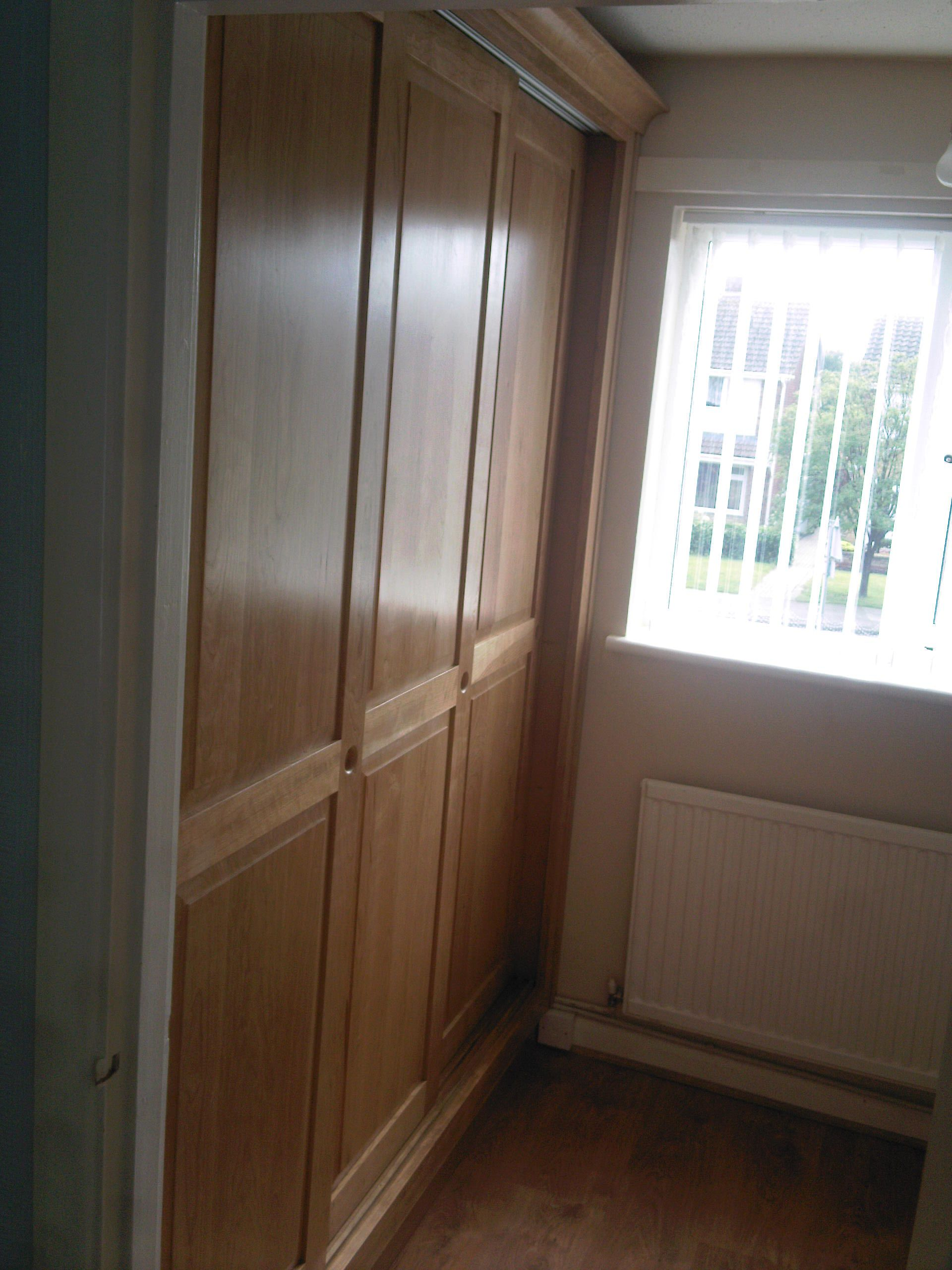 Cherry Wardrobes maximising space in a small bedroom.