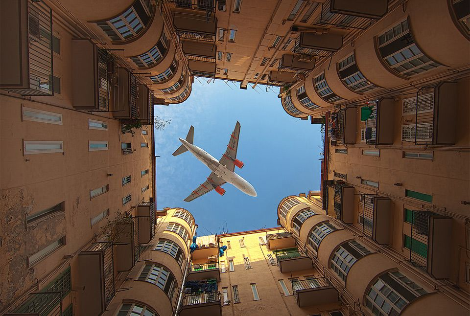 Really cool shot of a plane over buildings